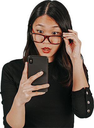 Woman with glasses looking at her smartphone intensely