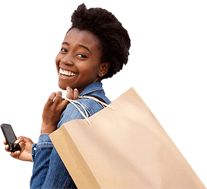 Smiling woman with a grocery bag over her sholder and holding a smartphone