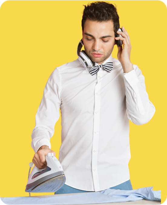 Dressed-up man ironing a shirt and holding his headphones